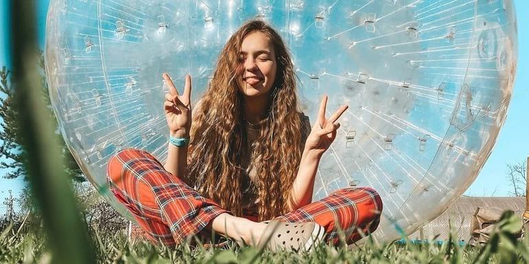 Маша Маева сидит на траве